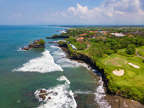 Aerial view to Tanah lot temple and golf club with green hills,